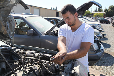 Pick-n-Pull customer pulling used auto parts from a broken junk car