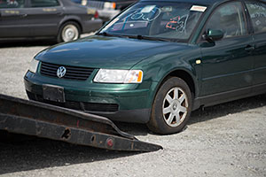 A green junk car being loaded onto a tow truck