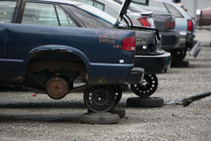 Blue junk car on jacks in an auto salvage yard