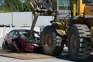 A red junk car is being picked up through the windshield by a tractor
