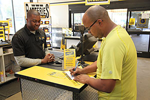 Pick-n-Pull customer signing up for toolkit rewards program in the store